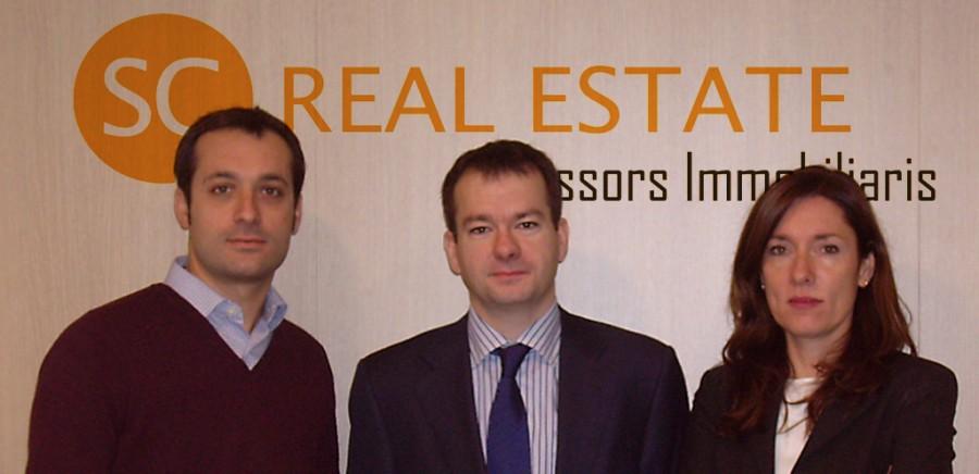 Equipo de Sc Real Estate frente al logo corporativo